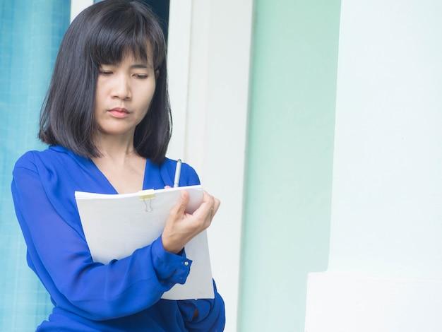 Mulher escrevendo com escritório de roupas de trabalho.
