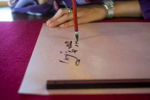 Mulher escrevendo com tinta em papel japonês Foto gratuita