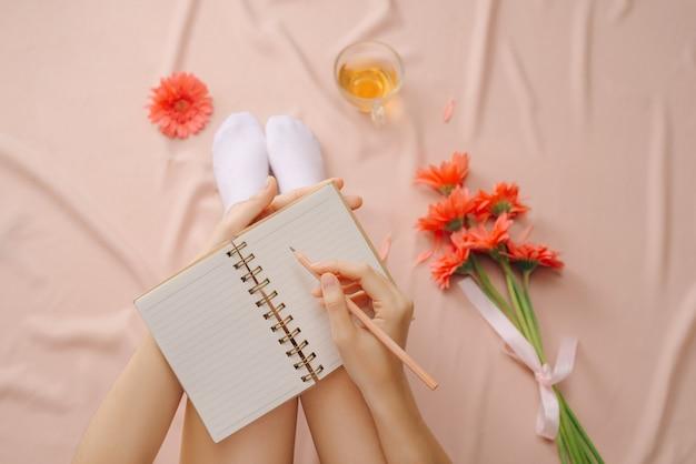 Mulher escrevendo em um bloco de notas em branco