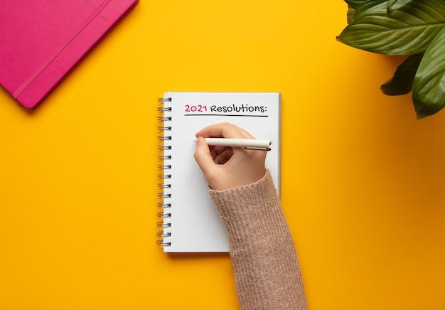 Mulher escrevendo em um caderno de resoluções de ano novo de 2.021