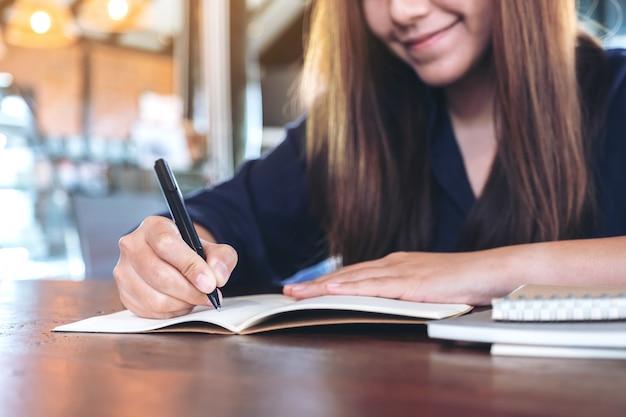 Mulher escrevendo em um caderno em branco na mesa de madeira