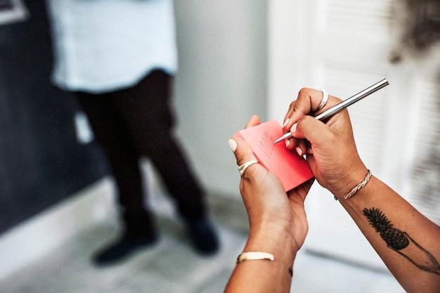 Mulher escrevendo em uma nota adesiva