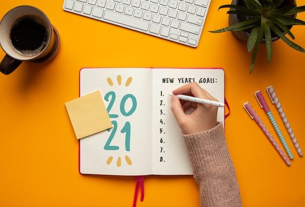 Mulher escrevendo metas em um caderno de ano novo de 2021