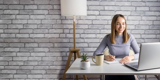 Mulher escrevendo no bloco de notas e usando o laptop em casa ou no escritório. bandeira.