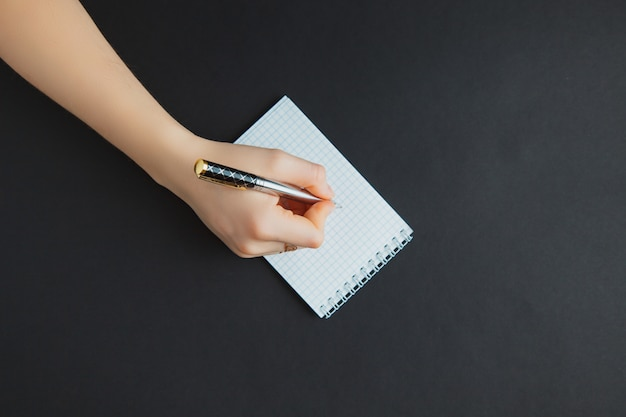 Mulher escrevendo no bloco de notas na mesa preta