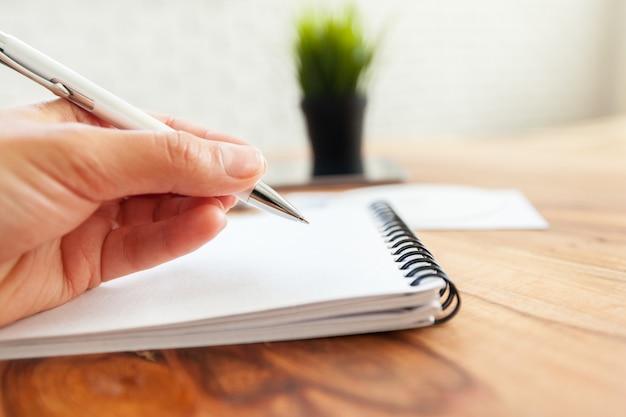 Mulher escrevendo no bloco de notas