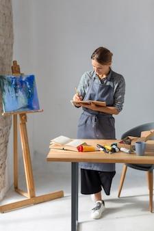 Mulher escrevendo no caderno em estúdio