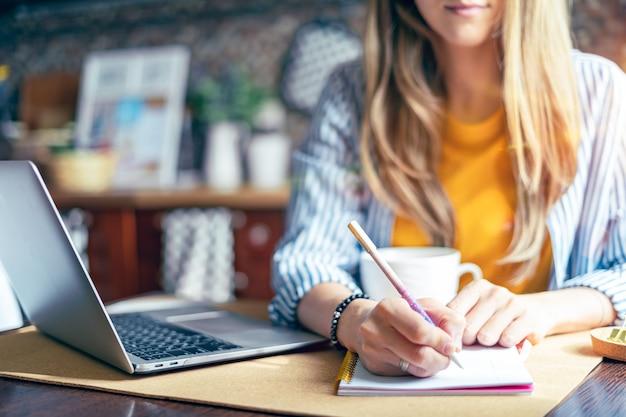 Mulher escrevendo no caderno na mesa com o laptop