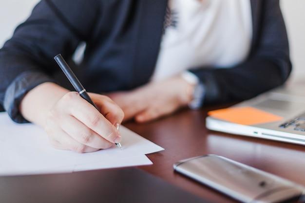 Mulher escrevendo no escritório