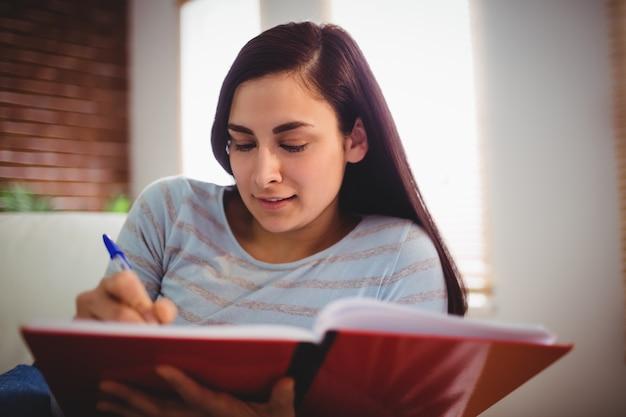 Mulher escrevendo no livro