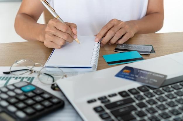 Mulher escrevendo no notebook com computador, calculadora e cartão de crédito na mesa, conta e conceito de economia.