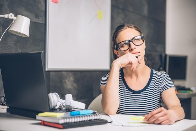 Mulher escrevendo notas e contemplando no escritório