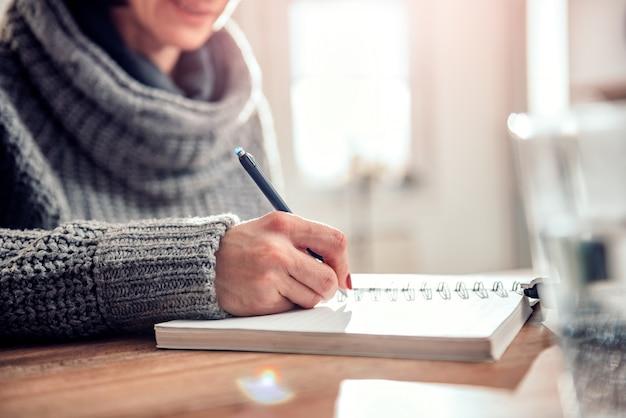 Mulher escrevendo notas no caderno no escritório