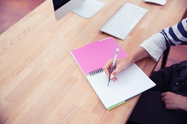 Mulher escrevendo notas no escritório