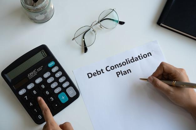 Mulher escrevendo o plano de consolidação da dívida em papel enquanto usa a calculadora na mesa. copie o espaço, vista superior.