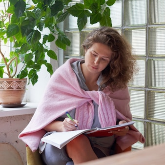 Mulher escrevendo páginas de manhã no caderno, registro do dia de planejamento no diário.