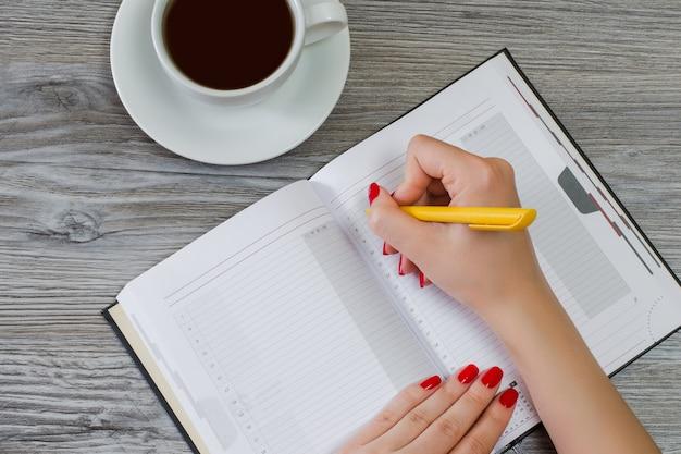 Mulher escrevendo redação no bloco de notas à mesa, a xícara de café no fundo, vista aérea