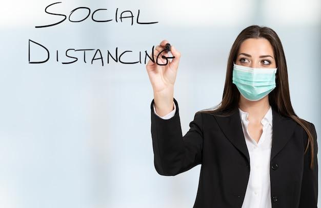 Mulher escrevendo social distancing na tela usando uma caneta, conceito de pandemia de coronavírus