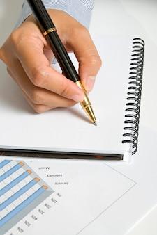 Mulher escrever na agenda em branco com caneta preta