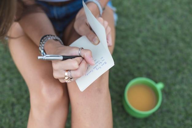 Mulher, escrita, com, caneta, branco, papel, com, xícara café