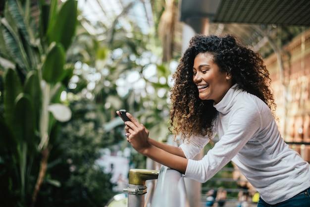 Mulher escura descascada adorável com penteado afro usando seu telefone.