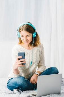 Mulher, escutar música, e, usando, smartphone