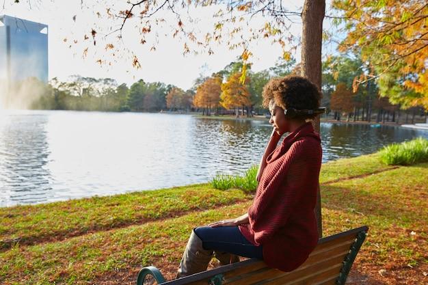 Mulher, escutar música, em, a, outono, parque