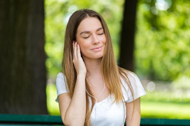 Mulher, escutar música, sentando, ona, banco, em, um, parque, em, um, quentes, verão, ensolarado, dia