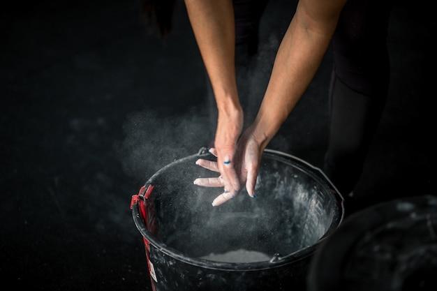 Mulher esfrega as mãos com giz e talco para que os dedos não escorreguem ou deslizem