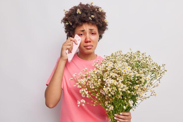 Mulher esfrega os olhos lacrimejantes com lenço de papel segurando buquê de flores de camomila sendo alérgica ao pólen isolado sobre o branco