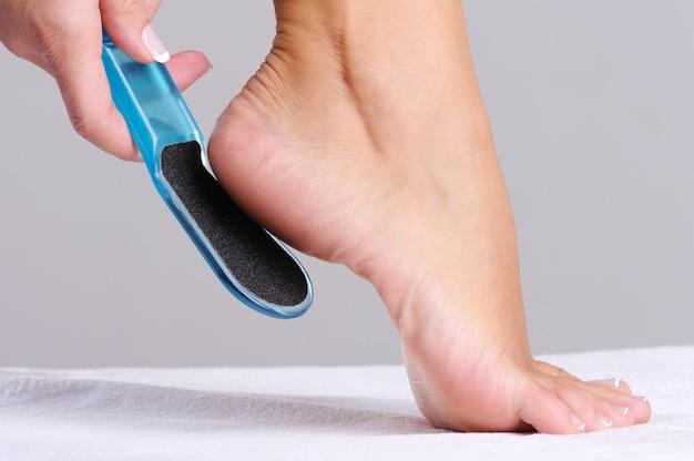 Mulher esfregando calcanhar em salão de beleza usa ferramenta para pedicure
