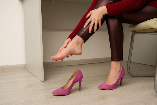 Mulher esfregando o pé sentada em uma cadeira