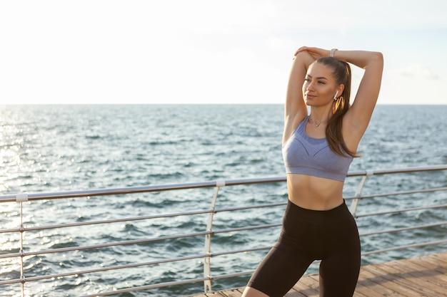 Mulher esguia com corpo perfeito praticando alongamento de mãos antes de treinar na praia ao nascer do sol