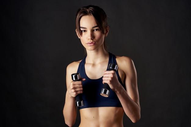 Mulher esguia com halteres na mão e fundo escuro de exercícios de treino