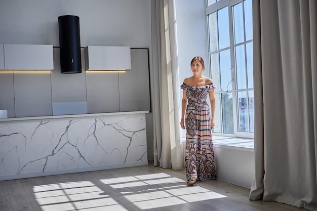 Mulher esguia de anos em um vestido longo de verão caminha pelo apartamento estúdio