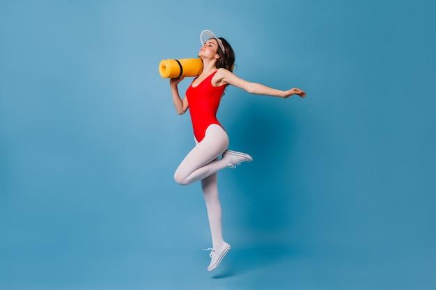 Mulher esguia de cabelos escuros em collant vermelho e meia-calça branca segurando um tapete de ioga