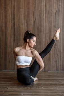 Mulher esguia e desportiva praticando alongamento de ioga na academia