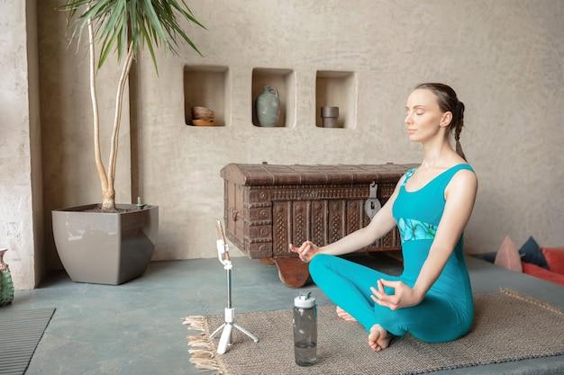 Mulher esguia e esportiva em roupas esportivas meditando em posição de lótus com o telefone e uma garrafa de água