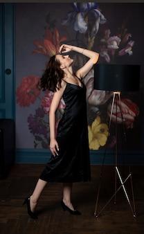 Mulher esguia e morena com vestido de seda preta posando em um quarto de designer com um abajur