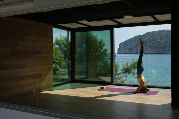 Mulher esguia praticando ioga em cabeceira apoiada no terraço
