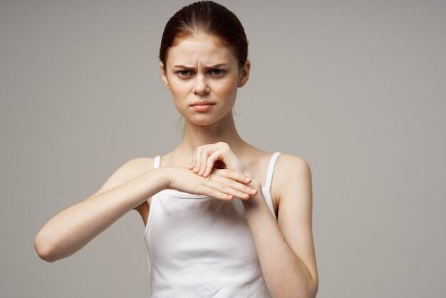 Mulher esguia tocando as mãos em vista recortada bege