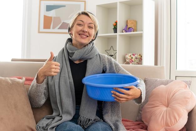 Mulher eslava doente sorridente com lenço em volta do pescoço, chapéu de inverno segurando balde e dedilhando sentado no sofá da sala de estar