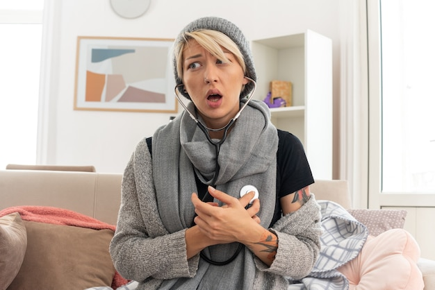 Mulher eslava jovem ansiosa com lenço no pescoço e chapéu de inverno, medindo seus pulsos com estetoscópio, olhando para o lado, sentada no sofá na sala de estar