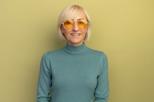 Mulher eslava loira bonita sorridente com óculos de sol olha para a câmera na cor verde oliva
