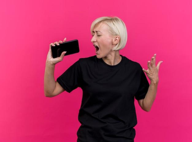 Mulher eslava loira de meia-idade cantando com os olhos fechados, mantendo as mãos no ar, usando telefone celular como microfone isolado na parede rosa