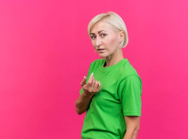 Mulher eslava loira de meia-idade em pé em vista de perfil, olhando para a frente, fazendo gesto de venha cá isolado na parede rosa com espaço de cópia