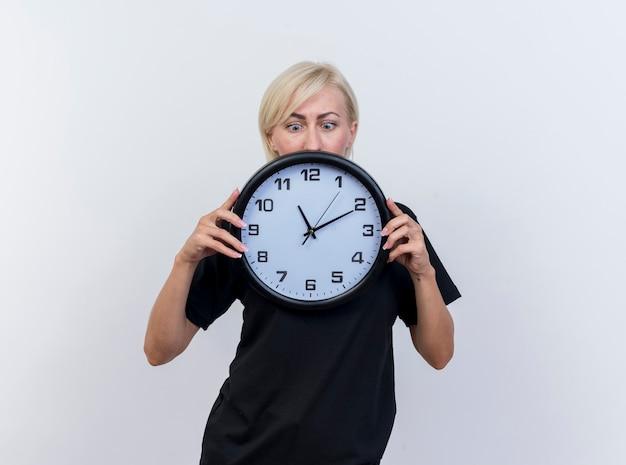 Mulher eslava loira de meia-idade impressionada segurando e olhando para o relógio isolado no fundo branco com espaço de cópia