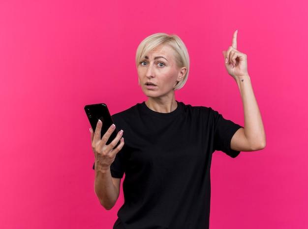 Mulher eslava loira de meia-idade impressionada segurando um celular, olhando para a câmera, apontando para cima, isolada em um fundo carmesim com espaço de cópia