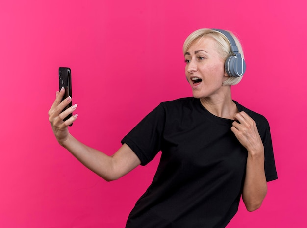 Mulher eslava loira de meia-idade impressionada usando fones de ouvido segurando e olhando para o celular segurando sua camiseta isolada na parede rosa