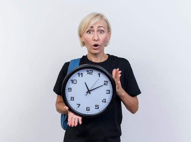 Mulher eslava loira de meia-idade impressionada usando uma mochila segurando um relógio e olhando para a câmera isolada no fundo branco com espaço de cópia